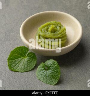 Dish with traditional Japanese horseradish paste and fresh wasabi leaves - Stock Photo