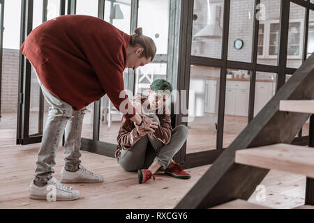 Woman sitting on floor and crying having fight with man