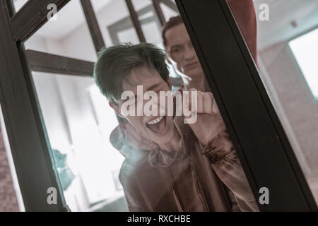 Wife with short hair cut screaming getting hit from husband - Stock Photo