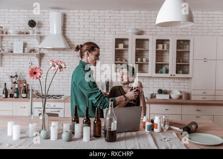 Husband feeling bad seeing his wife with empty bottles - Stock Photo