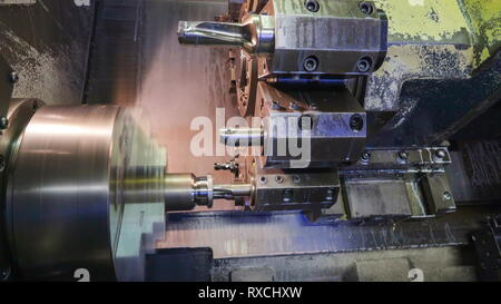 A big turning machine with different drill bits making a hole on the bottom of a metal tube inserted on a machine - Stock Photo