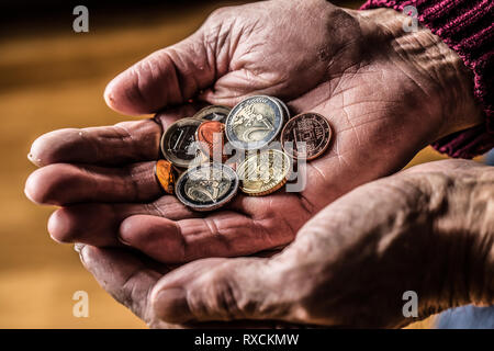 Pensioner man holding in hands euro coins. Theme of low pensions - Stock Photo