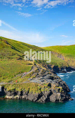 2 July 2018: Boscastle, Cornwall, UK - The South West Coast Path on the cliff tops near Boscastle, as a group of people walk down toward the harbour. - Stock Photo