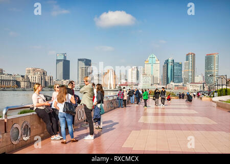 1 December 2018: Shanghai, China - Visitors walking on the bank of the Huangpu River on the Pudong side, opposite The Bund, Shanghai. - Stock Photo