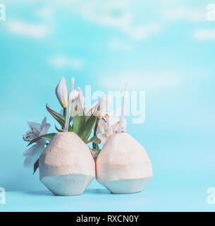 Two coconut cocktails in fresh coconuts at blue sky background. Summer tropical drinks - Stock Photo