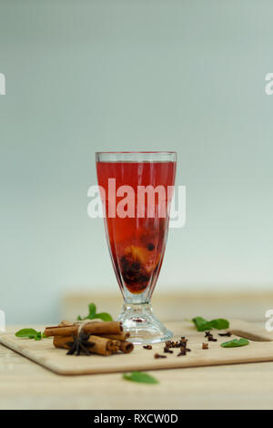 Cup of red hot vitamin tea on wooden table. winter hot seasonal drinks. - Stock Photo