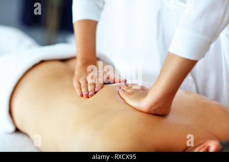 Handsome man having massage in spa salon - Stock Photo