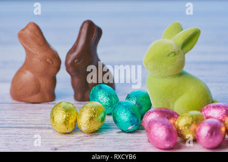 in the foreground an easter bunny beside wrapped colored shiny chocolate eggs, in the background two chocolate bunnies unwrapped on white wooden backg - Stock Photo