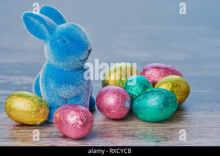blue easter bunny with wrapped chocolate eggs against white wooden background with copy space - Stock Photo