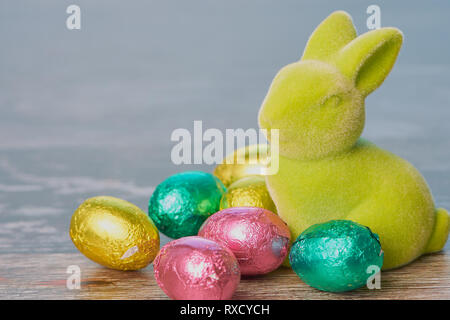 green easter bunny with wrapped chocolate eggs against white wooden background with copy space - Stock Photo