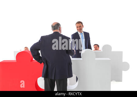 Business initiative volunteer concept . Business people hiding behind giant puzzle pieces . Brave one shaking hands with boss - Stock Photo