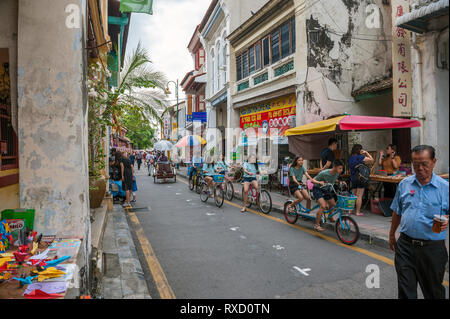 Tourists on Armenian Street in George Town, Penang. In the heart of the World Heritage district, the street is well known for its old clan temples and - Stock Photo