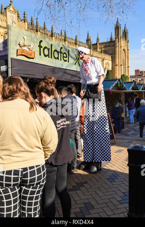 Super-sized chef (man on stilts) entertaining people looking at trade stalls - Wakefield Food, Drink & Rhubarb Festival 2019, Yorkshire, England, UK. - Stock Photo