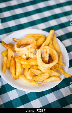 Deep fried squid with potato chips in local restaurant in Larnaca. Traditional cypriot meze food on Cyprus island. - Stock Photo
