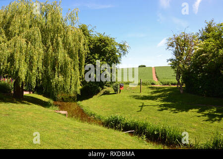 Pretty recreation ground / park with a stream running through it, on the egde of Lavenham town in Suffolk, UK. Sunny day. - Stock Photo