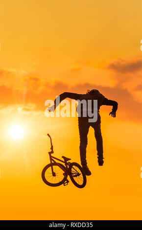 Silhouette of man dropping his bike while in a mid-air jump. Stunt gone wrong - Stock Photo