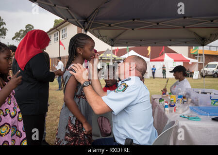 Sydney, Australia 9th, March 2019, NSW Police Sergent Robert Bourgault helps out with face painting at the Africultures Festival held in Wyatt Park, Lidcombe, Sydney. Despite the occasional shower of rain event goers were treated to music and entertainment, colourful market stalls and food from many of the represented nations. Contributor: Stephen Dwyer / Alamy Stock Photo Credit: Stephen Dwyer/Alamy Live News - Stock Photo