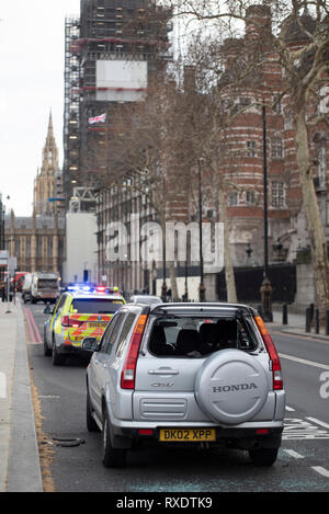 A suspicious car parked outside New Scotland Yard police headquarters on Victoria Embankment, Westminster, London, UK caused the police to lockdown and clear the the area around it and Westminster Bridge, including stopping river traffic on the Thames. Police broke the rear screen of the car to gain entry. - Stock Photo