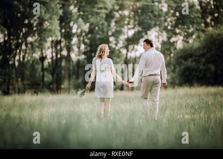 rear view. happy young couple walking on the lawn in the Park - Stock Photo