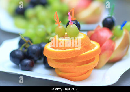 close up.plate with grapes and oranges on blurred background - Stock Photo