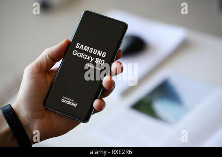 Man holding samsung galaxy s 10 in hand - Stock Photo
