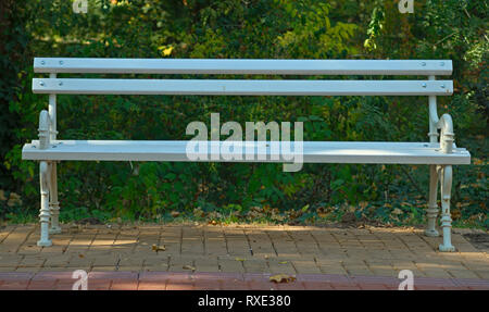 Front view on a white bench on red bricks with nature behind it - Stock Photo