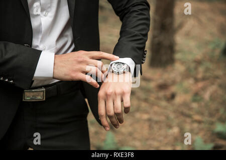 close-up of a businessman looking at wrist watch - Stock Photo