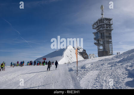 Engelberg, Switzerland - 3 March 2019: people getting ready to go skiing on mount Titlis over Engelberg in the Swiss alps - Stock Photo