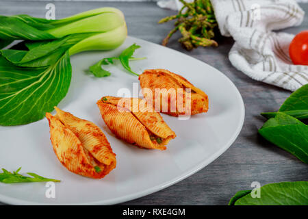 Big shells staffed pasta with meat tomato sauce and cheese - Stock Photo