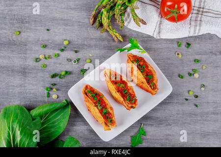Italian stuffed pasta shells with minced beef meat with herbs and tomato - Stock Photo