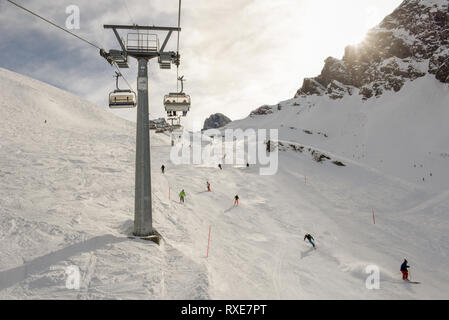 Engelberg, Switzerland - 3 March 2019: People skiing and going up the mountain by chairlift at Engelberg on the Swiss alps - Stock Photo