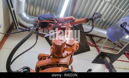 The welding robot inside the factory it is a big machine that is doing the welding works - Stock Photo