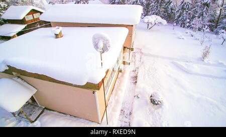 Aerial shot of the white beautiful snowy area. The communication dish in a tower filled with white snow - Stock Photo