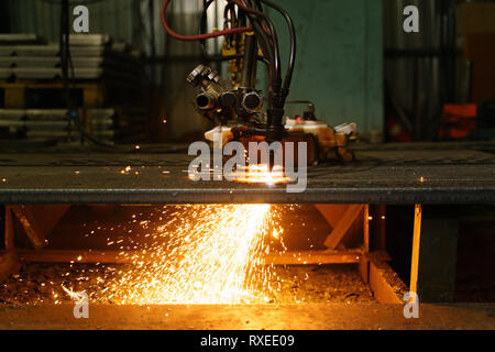 The machine cuts metal sheets with gas. Flying spray molten metal. Side view. - Stock Photo