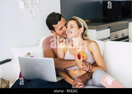 Cheerful and happy couple hugging and laughing at home lay down on the sofa - love and relationship concept with lifestyle healthy concept - technolog - Stock Photo