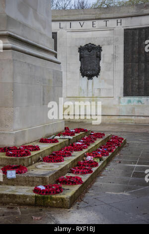 Poppies laid at the war memorial in Portsmouth, UK, after remembrance day parade - Stock Photo