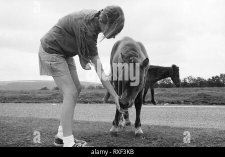 Young girl about 10/11, feeding grass to a pony, Dartmoor, Devon, UK..  Black and white film photograph, circa 1994.  MODEL RELEASED - Stock Photo