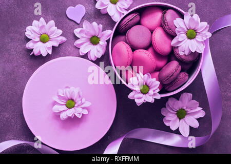 Purple and pink macaroons in a gift box on a beautiful purple background decorated with flowers. Top view. - Stock Photo