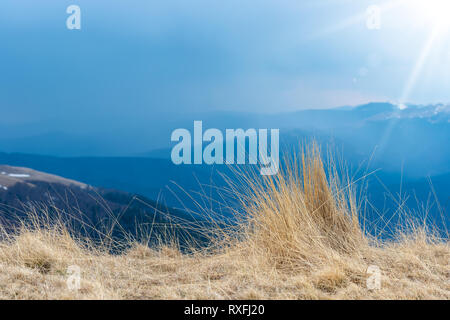 Natural landscape view of mountains, grass and strong sun rays, beautiful background for designs and cards. Early spring scenery of dried grass textur - Stock Photo