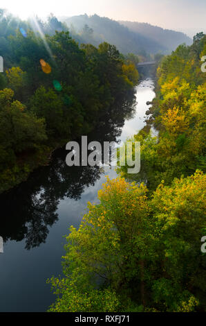 Magical summer morning sunrise over deep foggy forest along a river. First rays of sun through fog and trees on slopes. Scenic park landscape of misty - Stock Photo