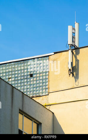 Mobile Phone Operator Antennas on the Top of the Facade of an Industrial Building Against the Blue Clear Sky. Copy Space. Communication Technology Con - Stock Photo
