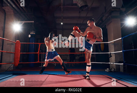 Handsome sportsman kickboxer practicing kickboxing with sparring partner in the ring at the sport club - Stock Photo
