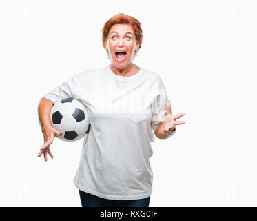 Atrractive senior caucasian redhead woman holding soccer ball over isolated background very happy and excited, winner expression celebrating victory s - Stock Photo