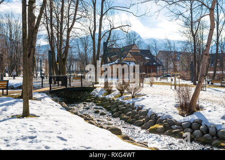 Zakopane, Poland - February 21, 2019. Park in the city covered with snow with a beautiful wooden house. Visible trees, brook with a rocky shore, bridg - Stock Photo