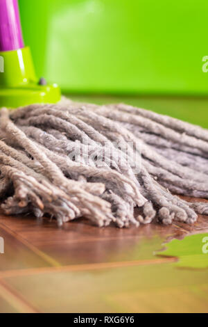 Rope mop on the tile floor and a puddle of water. Home cleaning and cleanliness concept - Stock Photo