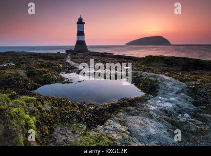 Trwyn Du Lighthouse or Penmon Point Lighthouse & Puffin Island at sunrise, Penmon, Anglesey, North Wales, UK - Stock Photo