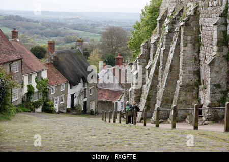 View down steep Gold Hill, with quaint and thatched roofed cottages in Shaftesbury, Dorset, England, UK - Stock Photo