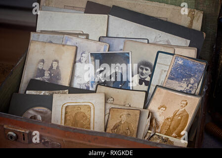 A suitcase full of old vintage photographs in the window of a charity shop in  Edinburgh, Scotland, UK. - Stock Photo