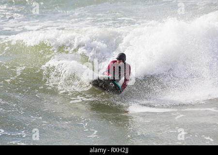 Bournemouth, Dorset, UK. 10th Mar 2019. UK weather: big waves and plenty of surf create ideal surfing conditions for surfers at Bournemouth beach on a windy day with some sunshine. Surfer lying down on surf board riding the waves.   Credit: Carolyn Jenkins/Alamy Live News - Stock Photo