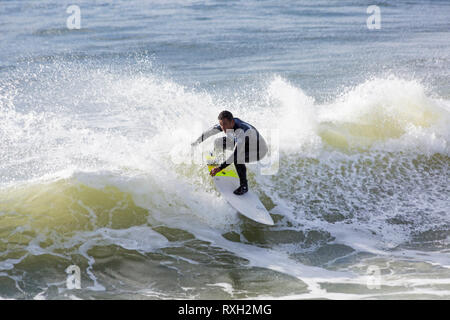 Bournemouth, Dorset, UK. 10th Mar 2019. UK weather: big waves and plenty of surf create ideal surfing conditions for surfers at Bournemouth beach on a windy day with some sunshine. Surfer in action on surf board riding the waves.   Credit: Carolyn Jenkins/Alamy Live News - Stock Photo
